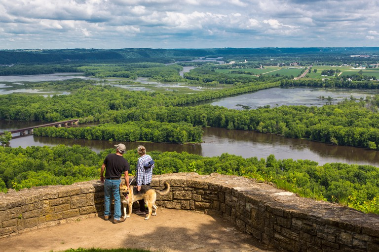 Couple with dog at scenic overlook of confluence of Wisconsin & Mississippi Rivers from Wyalusing State Park in Wisconsin