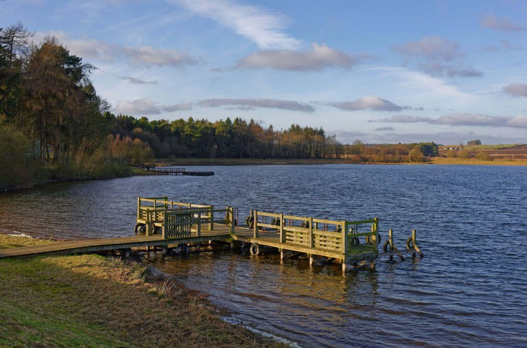 Two empty wooden piers on the banks of the Reservoir at Monikie Country Park on a sunny afternoon in February.