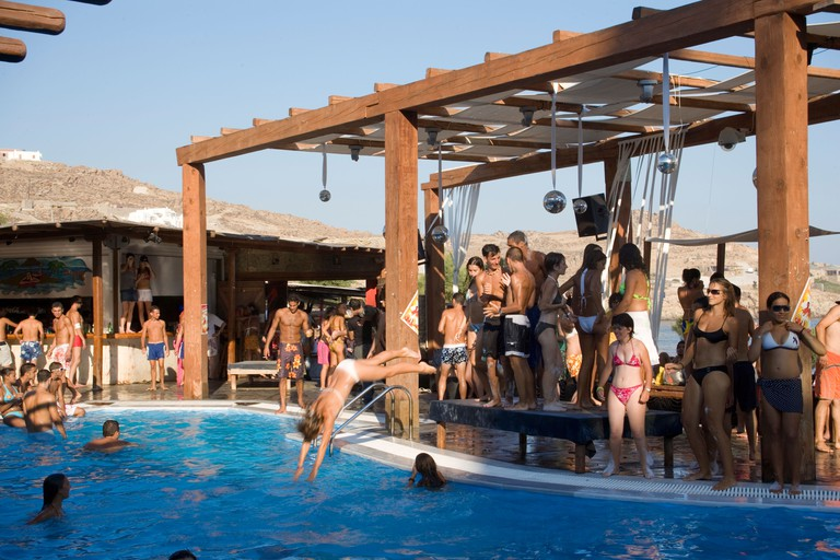 Young people dancing during a beach party at a pool of the Paradise Club Paradise Beach Mykonos Greece