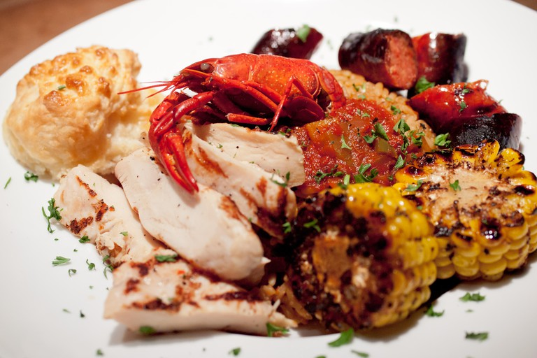 Cajun food: a plate of jambalaya with rice, a crawdad (crayfish), chicken, andouille sausage, and corn.
