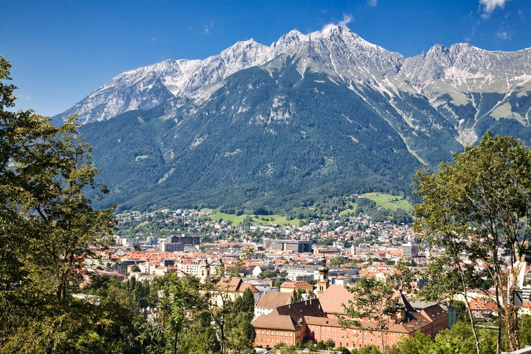 Innsbruck, Austria sits in a valley in front of steep mountains.