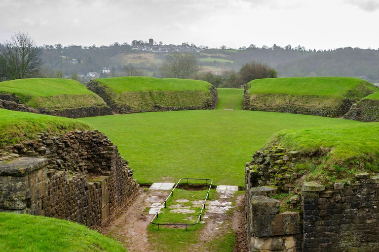 Grass covered remains of the ancient Roman amphitheatre at Caerleon Roman Fortress, Isca, near Newport, Gwent, south Wales