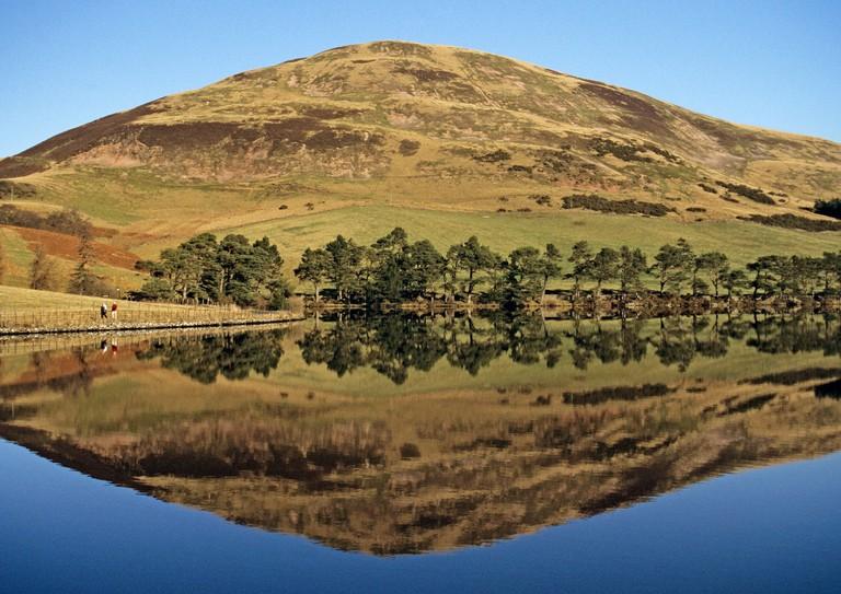 Walkers passing Glencorse Reservoir in the Pentland Hills near Edinburgh The hill is Castlelaw Hill
