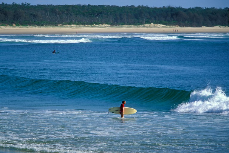 Surfer and shore break at Crescent Head a famous surf location near Kempsey on the mid north coast of New South Wales Australia