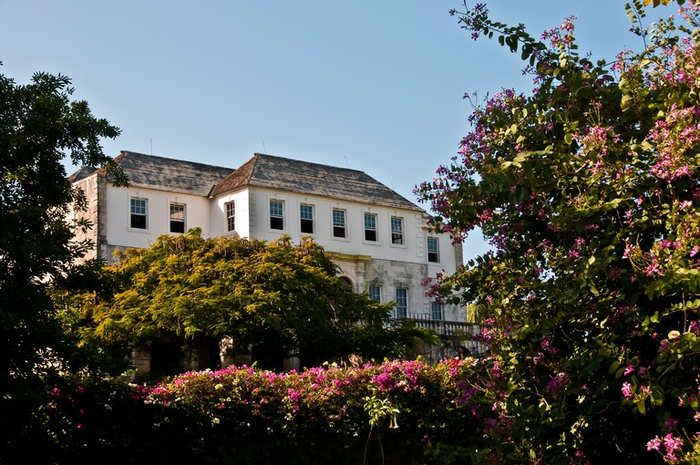Exterior of Rose Hall Great House surrounded by colorful red flowers, landmark Montego Bay tourist attraction