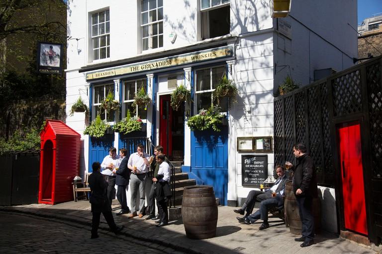 Patrons drinking outside The Grenadier pub in Belgravia.  London, UK.