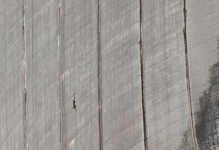 """A bungee jumper jumps off Valle Verzasca """"Contra"""" dam at lago di Vogorno, Ticino, Switzerland"""