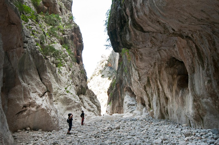 People hike inside Gorropu gorge, one of the highest canyon in Europe, Supramonte zone of Urzulei and Orgosolo, Sardinia, Italy. Image shot 05/2014. Exact date unknown.