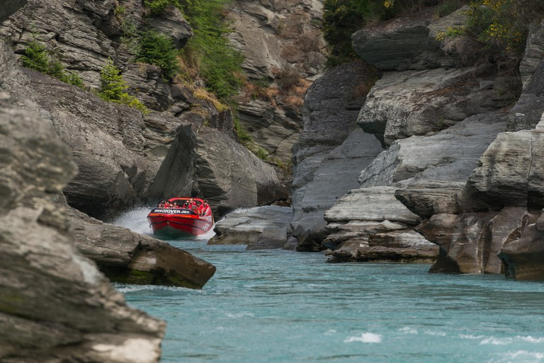 Group of tourists Jet boating on Shotover River at Arthurs Point, Queenstown, Otago, New Zealand's South Island.