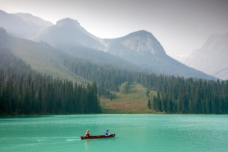 Tourists in red canoe on Emerald Lake, Yoho National Park, British Columbia, Canada