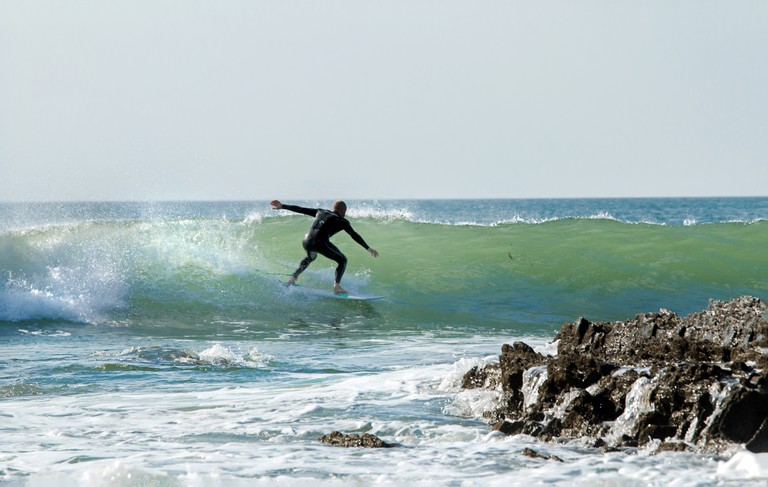 Surfer riding the waves close to the rocks at Croyde Bay, Devon.