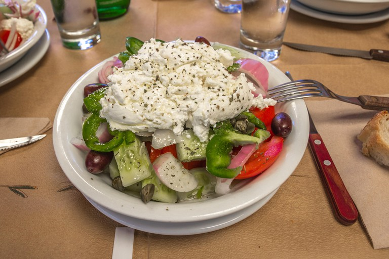 Ready to eat - Greek Salad with fresh tomatoes, cucumbers, red onions, green peppers, olives and a huge dollop of creamy Naxos cheese in a white bowl