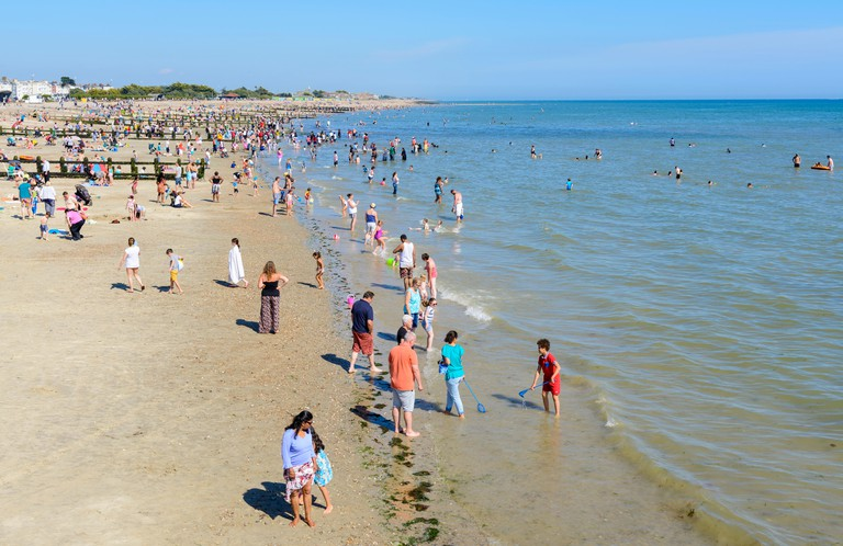 People swimming in the sea at a beach on a summer's day at the seaside in Littlehampton, West Sussex, England, UK.