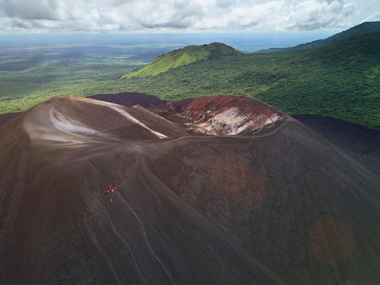 Volcano boarding theme. Above view on people doing extreme sport