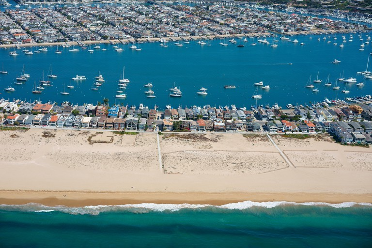 BALBOA PENINSULA IN THE FOREGROUND WITH BALBOA ISLAND BEHIND (aerial view). Newport Beach, Orange County, California, USA.