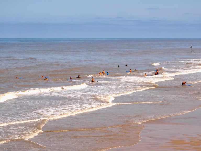 Group of surfers having tuition and safety instructions in Cromer beach in Norfolk