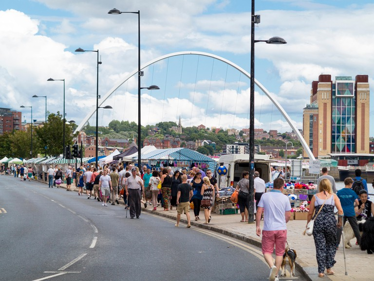 Newcastle Quayside market with Millennium Bridge and Baltic Gallery in background