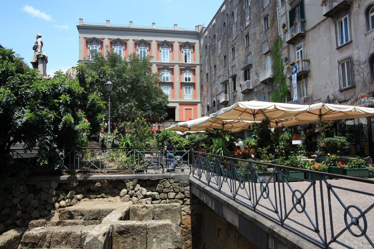 People enjoying life underneath sunshades of a cafe at Piazza Bellini in Napoli, Italy, right next to some excavations from the ancient Roman Empire