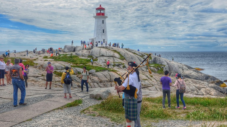 Peggy's Cove, Nova Scotia, Canada: A bagpiper plays for tourists near the lighthouse at the popular tourist destination of Peggys Cove, Nova Scotia