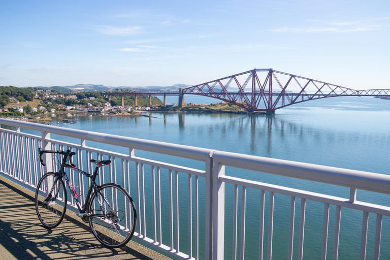 A road bicycle lent against the railing of the Forth Road Bridge with North Queensferry in the background.