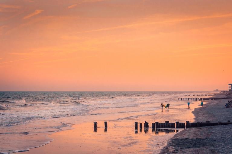 Surfers walk along the beach at sunset, April 3, 2015, in Folly Beach, South Carolina. (Photo by Carmen K. Sisson/Cloudybright)