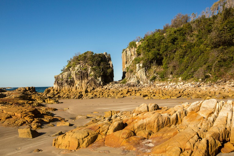 Australian coastal landscape with deserted sandy beach and rocks under blue sky at Diamond Head in Crowdy Bay National Park NSW