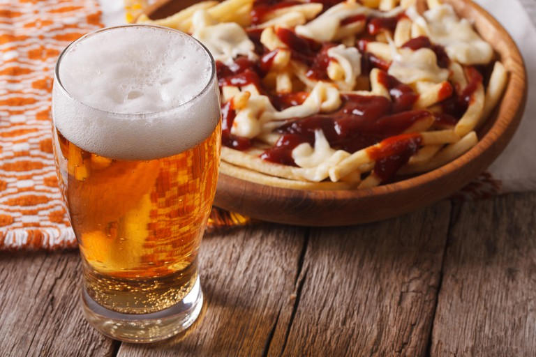 Canadian food: beer and fries with sauce close-up on the table. horizontal
