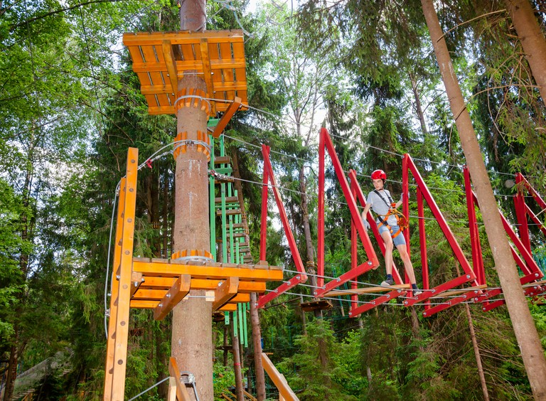 Teenager boy passing hanging rope bridge obstacle at a ropes course in outdoor treetop adventure park