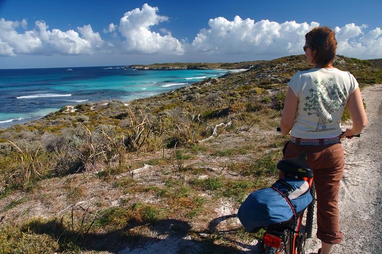 Female cyclist admires view Rottnest Island Western Australia No MR