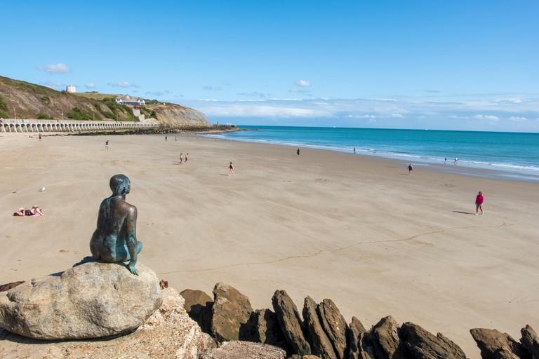 The Folkestone mermaid by artist Cornelia Parker overlooking the wide expanse of Sunny Sands Beach, Folkestone, Kent, UK