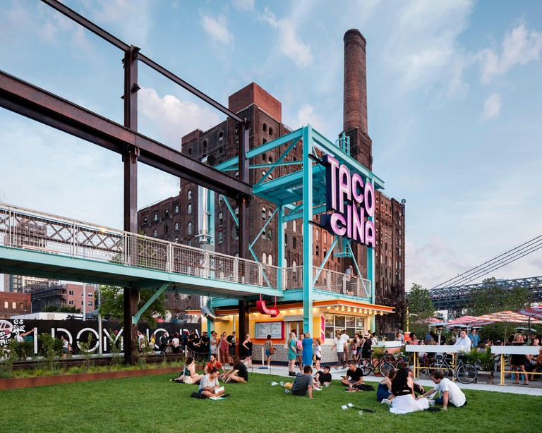 Tacocina restaurant against the backdrop of the former Domino Sugar Factory. Domino Park, Brooklyn, United States. Architect: James Corner Field Opera