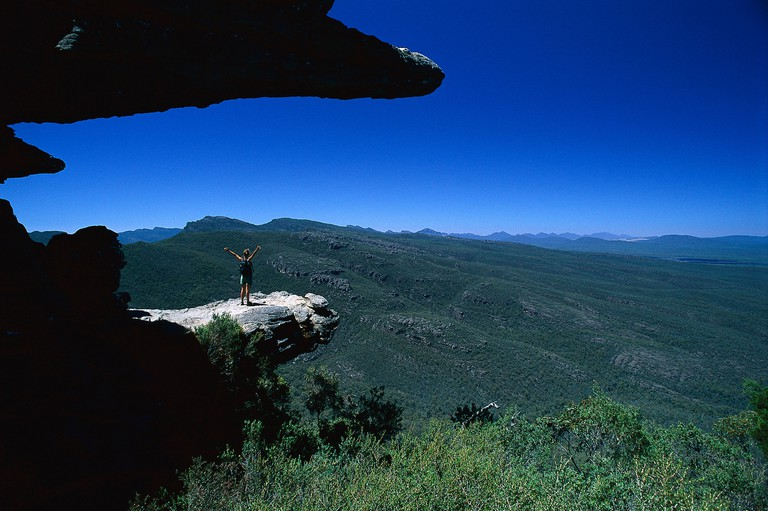 A woman standing on a rock spur under blue sky, The Balconies, Reeds Lookout, Serra Range, Grampians National Park, Victoria, Au