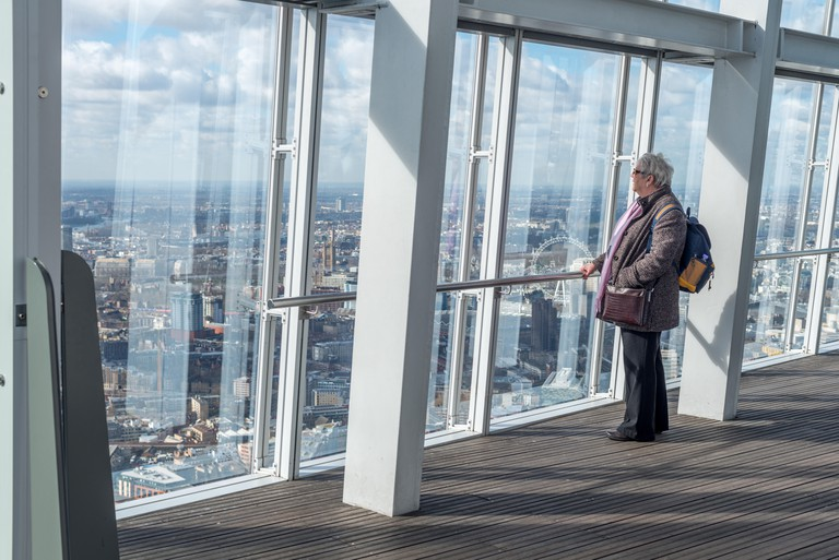 A woman looks out at The View From The Shard, London, UK