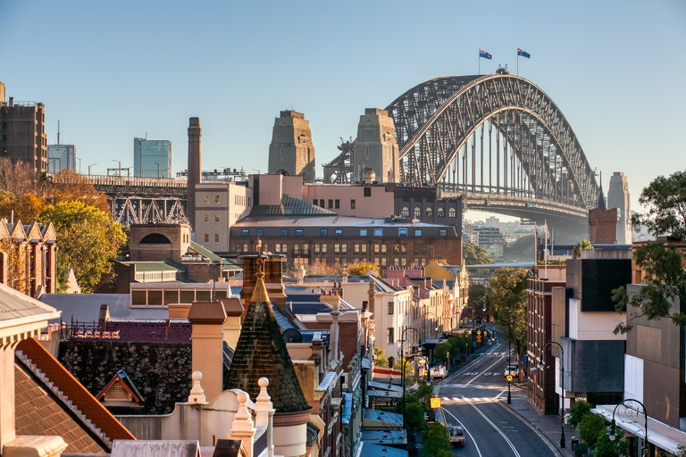 The Rocks, Sydney, George Street, Sydney Harbour Bridge and buildings with blue sky. Famous Historic Downtown street. Sunny Morning.