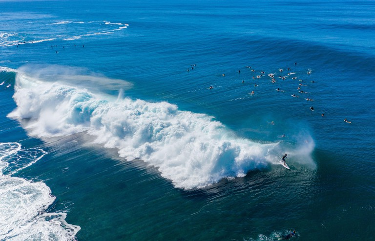 Surfers waiting for the big wave in the sea at Banzai Pipeline on north coast of Oahu, Hawaii