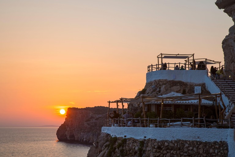 Sunset over terraces at Cova d'en Xoroi, a bar and night club set in natural caves, Cala en Porter, Menorca, Spain