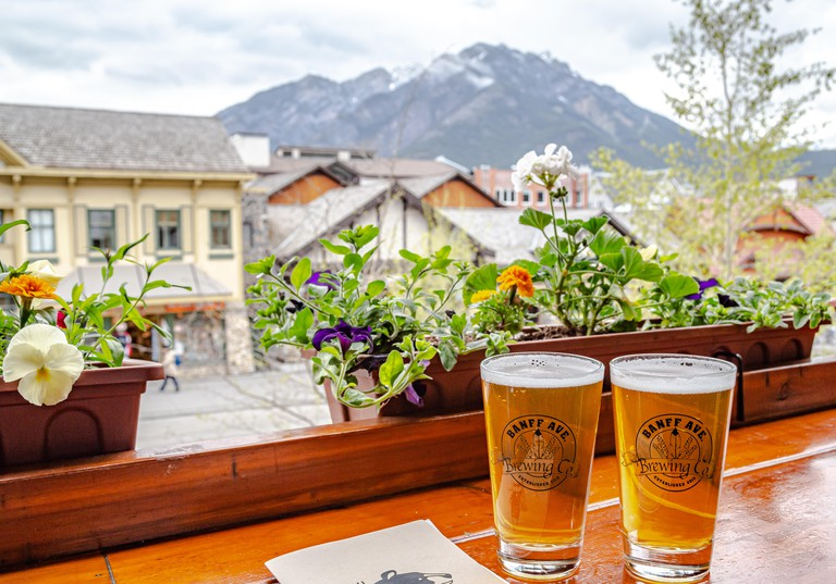 Enjoying beers on outside terrace of Banff Ave Brewing Co in Banff, Alberta