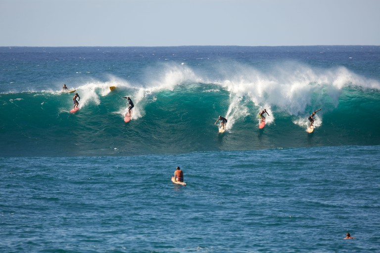 Many surfers ride a large wave at Waimea Bay, Oahu, Hawaii