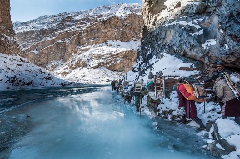 Bunch of porters are walking on the frozen Zanskar River during Chadar trek