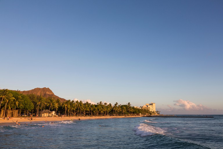 Queen's Surf Beach in Waikiki with a view Diamond Head at sunset.