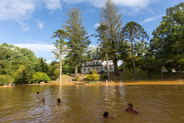 People bathing in the thermal pool of Terra Nostra Garden. Parque Terra Nostra. Furnas. Sao Miguel