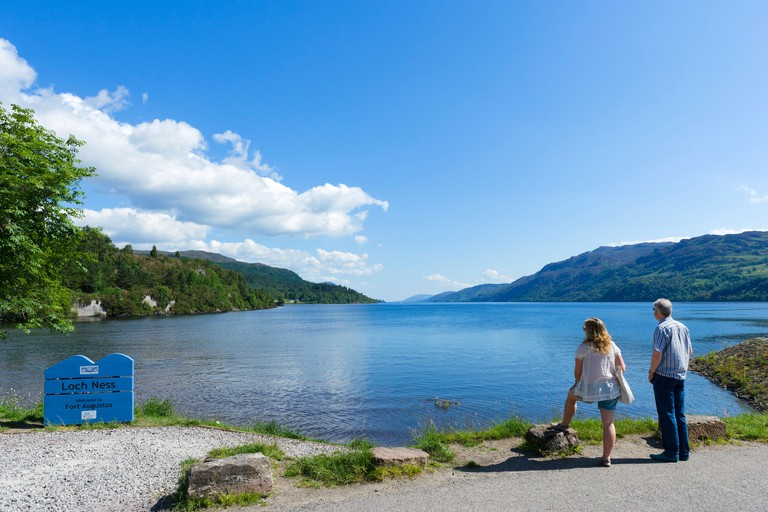 Couple looking out over the southern end of Loch Ness in Fort Augustus, Highland, Scotland, UK