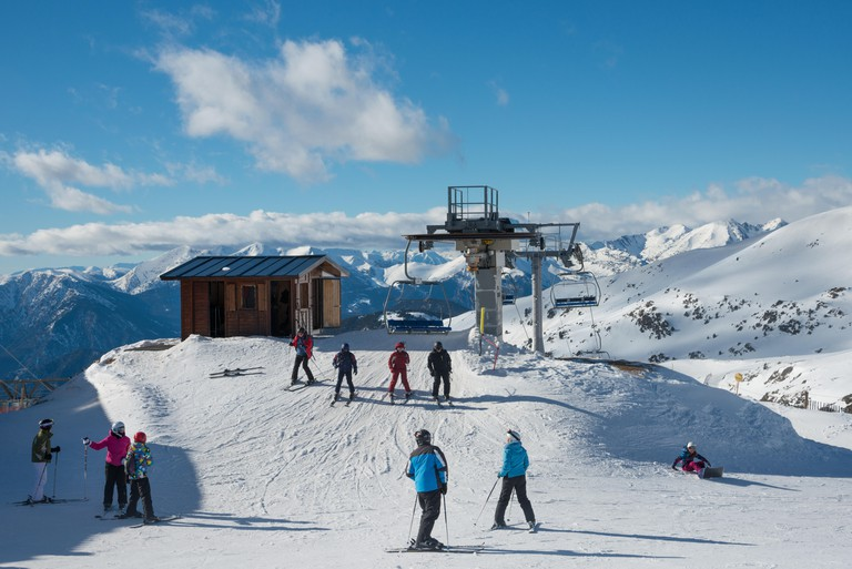 Skiers exiting a chair lift above Soldeu and El tarter, Grandvalaria ski area, Andorra, Europe