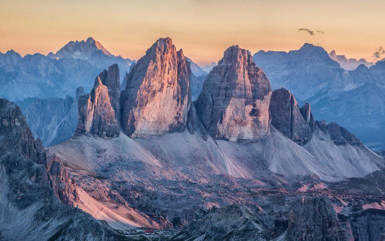 Beautiful view of famous Tre Cime di Lavaredo mountain summits in the Dolomites mountain range illuminated in beautful golden evening light at sunset