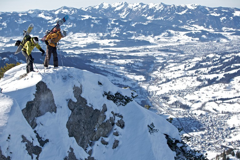Two snowboarders standing on a mountain top, Oberjoch, Bad Hindelang, Bavaria, Germany