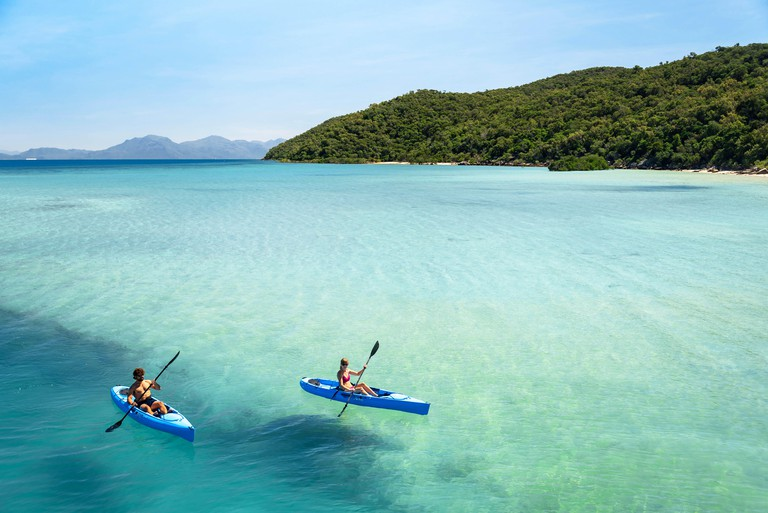 A couple kayaking in the turquoise lagoon of Orpheus Island, Queensland, Australia.