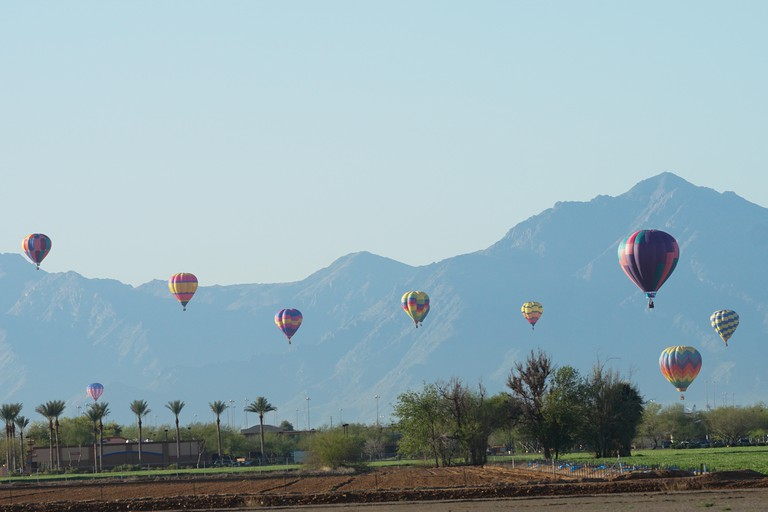 Hot air balloons rise in the sky in Phoenix, Arizona.