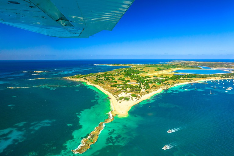 Aerial view of Rottnest Island in Australia. Scenic flight with wing of plane over famous tourist destination of Western Australia. Rottnest Island is