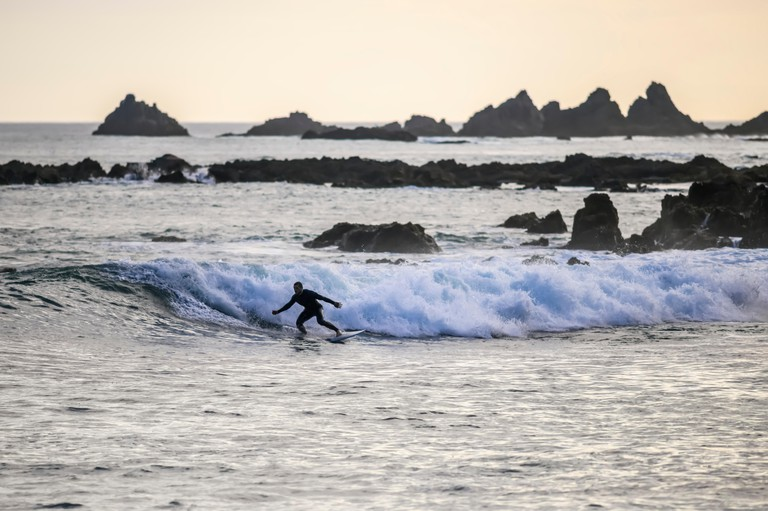 Surfing at dusk in Houghton Bay; Wellington, New Zealand