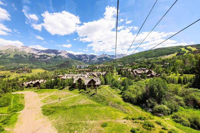 Telluride small town in Colorado with high wide angle above view of city cityscape from free gondola to mountain village in summer and trail path